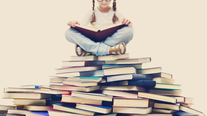 Girl reading on top of pile of books